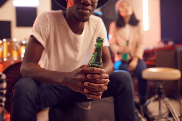 Portret w połowie sekcji modny afrykański mężczyzna trzyma butelkę piwa