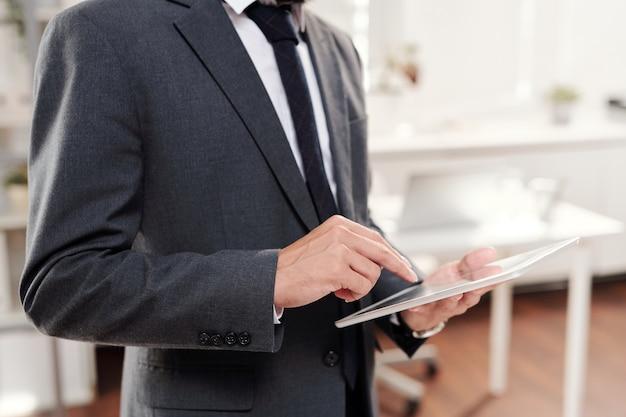 Portret w połowie sekcji nie do poznania biznesmen sukcesu, trzymając cyfrowy tablet, miejsce