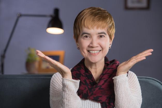Portret w średnim wieku kobieta siedzi w domu