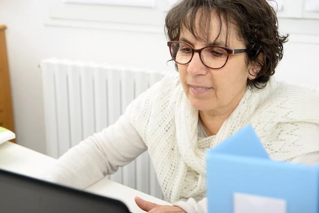 Portret w średnim wieku kobieta używa laptop