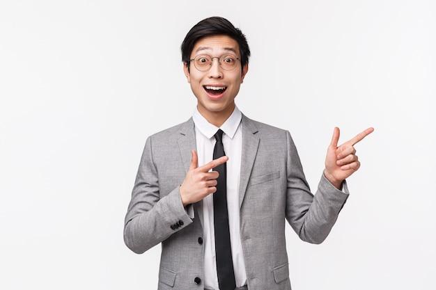 Portret w talii podekscytowany i zaskoczony, szczęśliwy azjatycki biznesmen w szarym garniturze, pokazujący coś niesamowitego, świetną reklamę, baner promocyjny po prawej stronie miejsca na kopię na białej ścianie