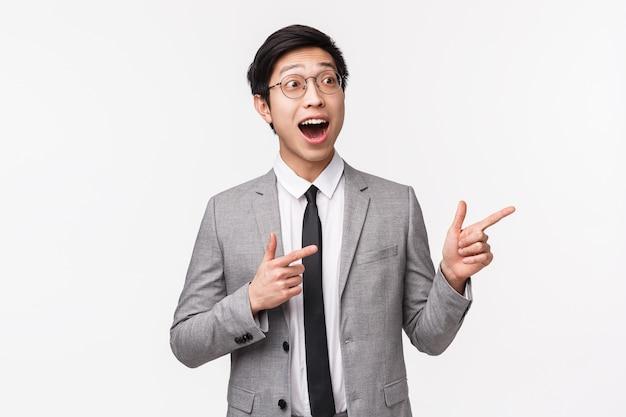 Portret w talii podekscytowany, zaskoczony i szczęśliwy młody emocjonalny azjatycki kierownik biura, biznesmen w szarym garniturze, widząc coś niesamowitego, wskazując i patrząc w prawo z opuszczoną szczęką na białej ścianie