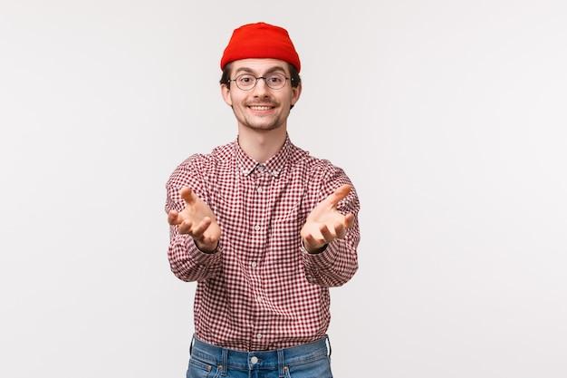 Portret w talii przyjemny zabawny młody człowiek z brodą w czerwonej czapce, trzymający się za ręce, jakby gotowy na przyjęcie czegoś, prezent, złapanie przedmiotu,
