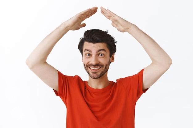 Portret w talii przystojny młody mężczyzna z włosiem, nosi czerwoną koszulkę podnoszącą ręce nad głową, robiąc dach domu, uśmiechając się radośnie, nie mogę się doczekać świętować święta w kręgu rodzinnym, biała ściana