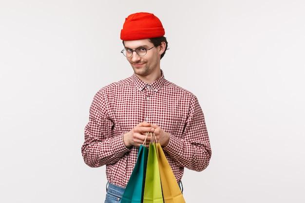 Portret w talii tajemniczy i zabawny słodki chłopak wyglądający przebiegłym aparatem i uśmieszkiem chytrze trzymającym torby na zakupy, mają doskonały pomysł, co kupić dla dziewczyny, idź do sklepu razem,