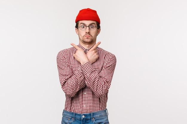 Portret w talii zabawny niezdecydowany facet w okularach i czerwonej czapce nie wiem co wybrać, wskazując bokiem na lewą i prawą reklamę, wyglądać na zakwestionowaną i niespokojną kamerę