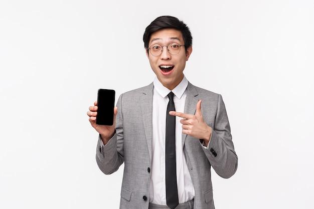 Portret w talii zdumiony i podekscytowany młody pracownik biurowy azji pokazujący coś niesamowitego na ekranie smartfona, trzymający telefon komórkowy i wskazujący na wyświetlacz z wrażoną twarzą