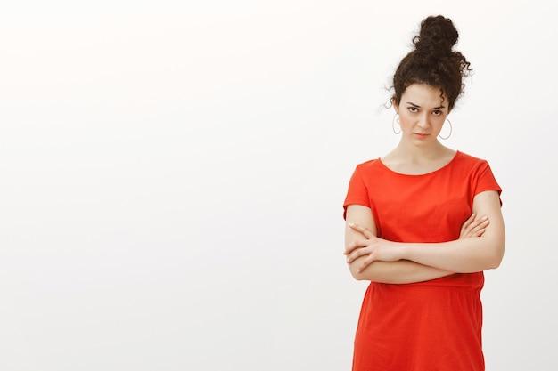 Portret wątpliwej atrakcyjnej miejskiej kobiety z kręconymi włosami zaczesanymi w kok
