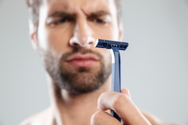 Portret wątpliwy skoncentrowany brodaty mężczyzna patrzeje żyletkę