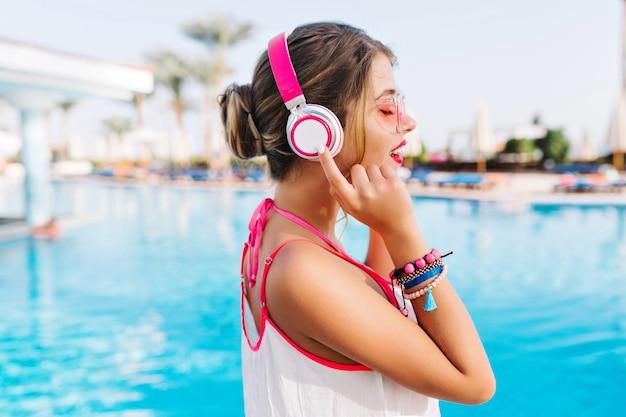 Portret wdzięcznej dziewczyny w białym podkoszulku spędza czas w pobliżu odkrytego basenu, ciesząc się muzyką i świeżym powietrzem