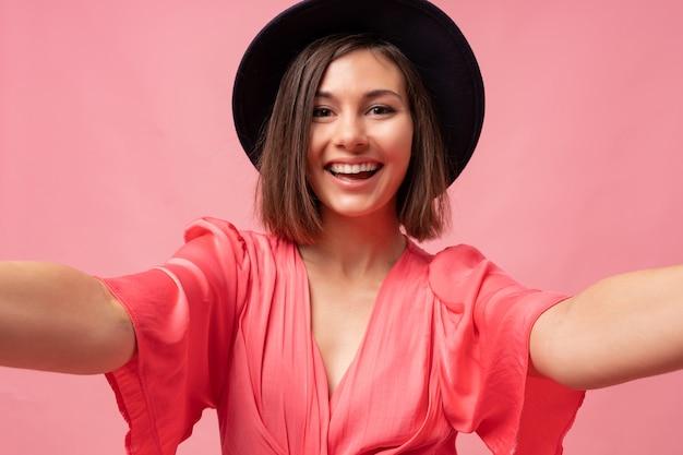 Portret wdzięku uśmiechnięta brunetka kobieta w różowej sukience