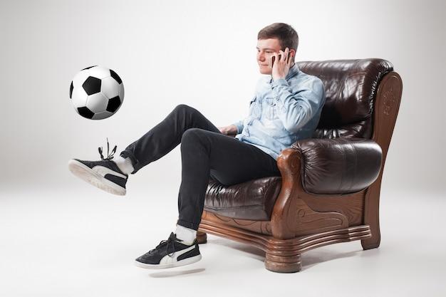 Portret wentylatora z piłką, trzymając pilota telewizora na białym tle