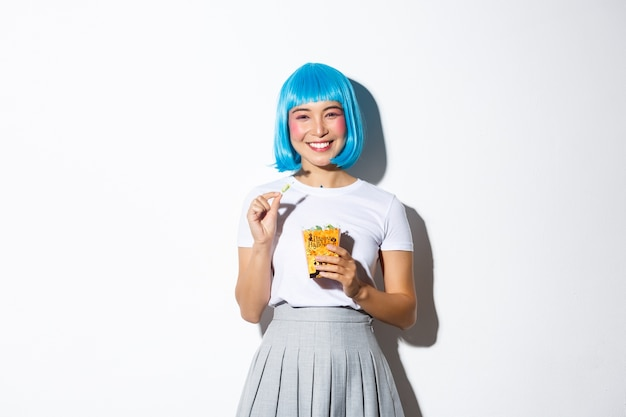 Portret wesoła azjatka w niebieskiej peruce świętująca halloween, jedząca słodycze z torby trick or treat, stojąca.