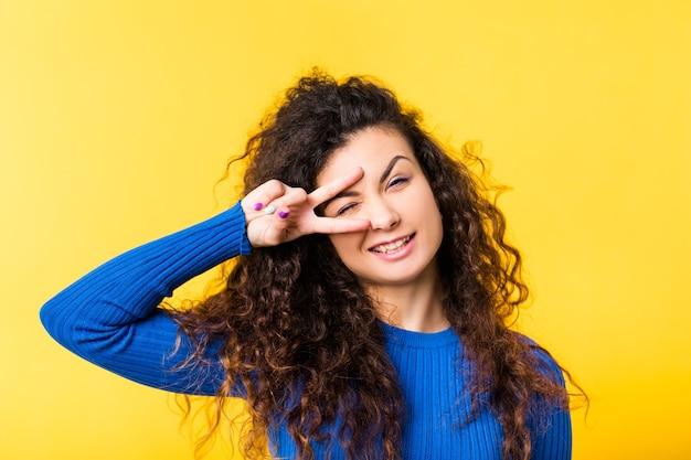 Portret wesoła brunetka dziewczyna z kręconymi włosami. śmieszne emocjonalne damy mrugając okiem przez palce w geście zwycięstwa, uśmiechając się.