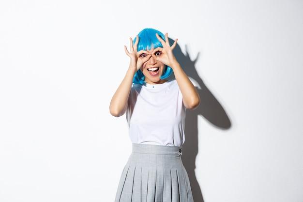 Portret wesoła dziewczyna azjatyckich, patrząc zdziwiony na aparat, ubrana w niebieską perukę i kostium na halloween party, stojąc.