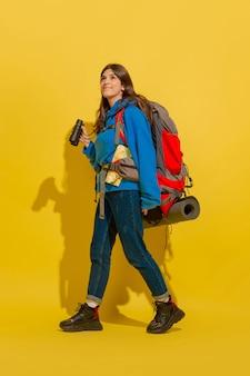 Portret wesoła dziewczyna młody turysta z torbą i lornetką na białym tle na żółtej ścianie studia
