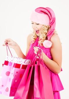 Portret wesoła dziewczyna pomocnika santa z torby na zakupy