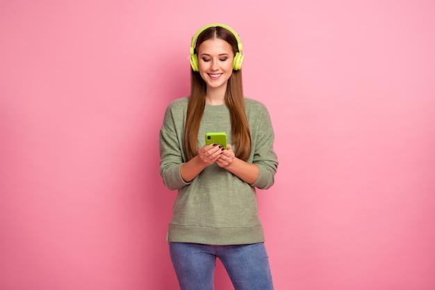 Portret wesoła dziewczyna używa telefonu komórkowego ma słuchawki do słuchania muzyki