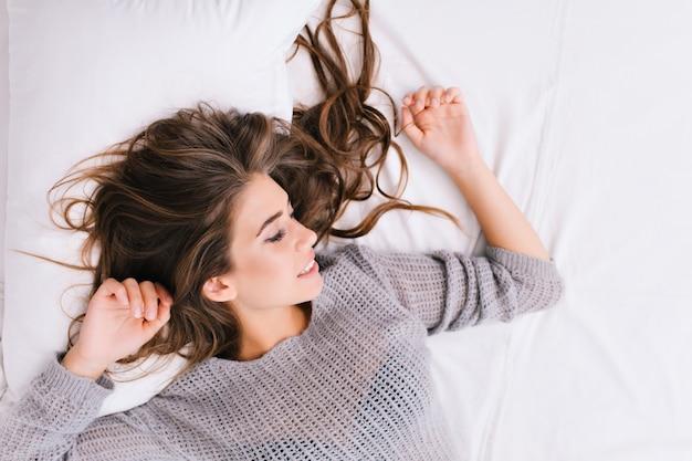 Portret wesoła dziewczyna z długimi brunetkami na biały zły. dzień dobry, pozytywne emocje, uśmiech z zamkniętymi oczami, chłodzenie w domu, marzenie. miejsce na tekst.