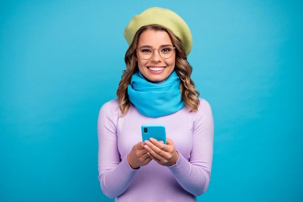 Portret wesoła dziewczyna za pomocą aparatu wygląd smartfona na turkusowym tle
