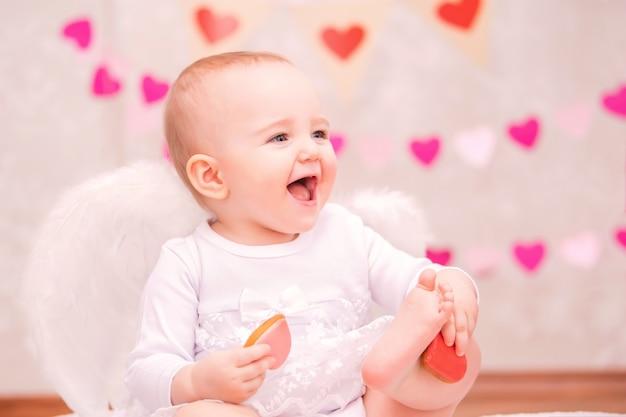 Portret wesoła dziewczynka z białymi skrzydłami z piór, jedząca ciasteczka w kształcie serca