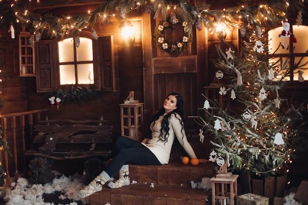 Portret wesoła i pozytywna kobieta o długich ciemnych włosach w swetrze, dżinsach i ciepłych skarpetkach trzymająca zapakowany prezent na boże narodzenie, siedząca pod udekorowaną choinką i opadami śniegu
