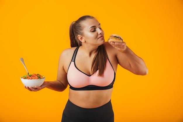 Portret wesoła kobieta fitness z nadwagą, noszenie odzieży sportowej, stojącej na białym tle nad żółtą ścianą, trzymając miskę z sałatką i burger