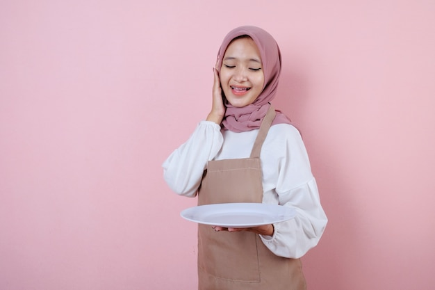 Portret wesoła młoda azjatycka kobieta szuka białego naczynia lub talerza