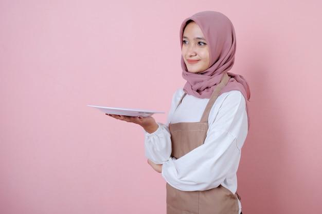 Portret wesoła młoda azjatykcia kobieta z białym naczyniem lub talerzem