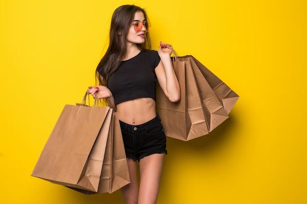 Portret wesoła młoda blondynka w letni kapelusz i okulary przeciwsłoneczne, trzymając torby na zakupy na żółtej ścianie