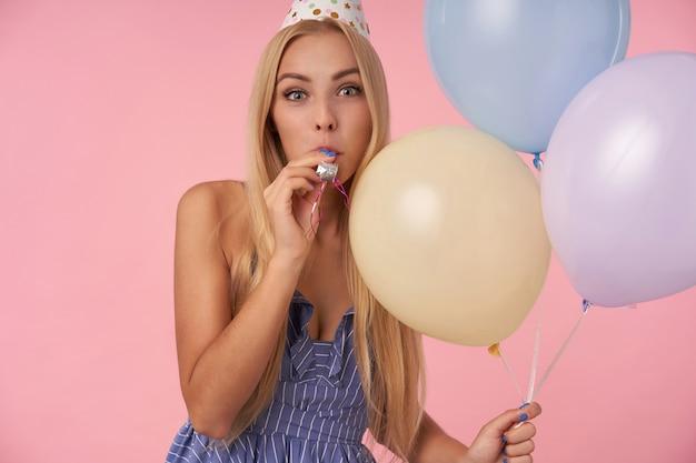 Portret wesoła młoda blondynka z długimi włosami, ubrana w strój holday i trzymająca wielobarwne balony, patrząc na kamerę z radością i dmuchając w róg imprezowy, pozując na różowym tle