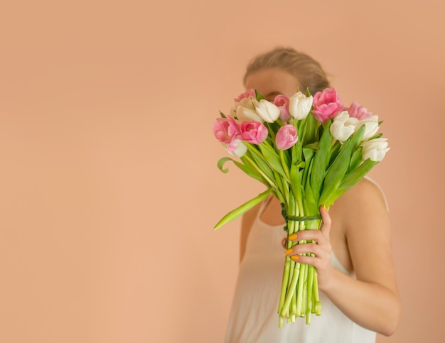 Portret wesoła młoda dziewczyna w sukni z bukietem kwiatów. portret pięknej dziewczyny w sukni z bukietem tulipanów