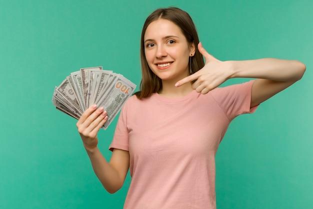 Portret wesoła młoda kobieta trzyma pieniądze i obchodzi na białym tle na niebieskim tle