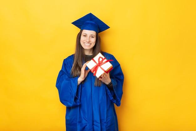 Portret wesoła młoda kobieta w niebieskiej szacie, kończąc studia i trzymając pudełko na żółtym tle