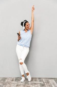 Portret wesoła młoda kobieta w okularach na białym tle, trzymając telefon komórkowy, słuchanie muzyki w słuchawkach, taniec