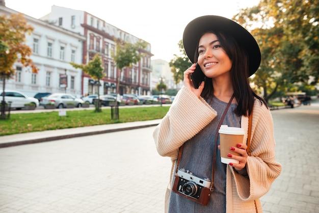 Portret wesoła stylowa kobieta trzymając kubek kawy
