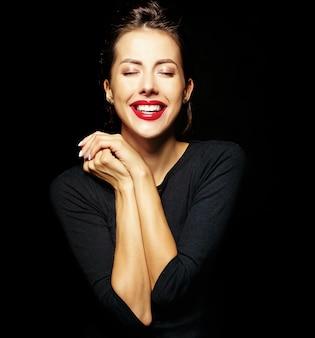 Portret wesoła uśmiechnięta dziewczyna moda w dorywczo czarne ubrania z czerwonymi ustami na czarnym tle