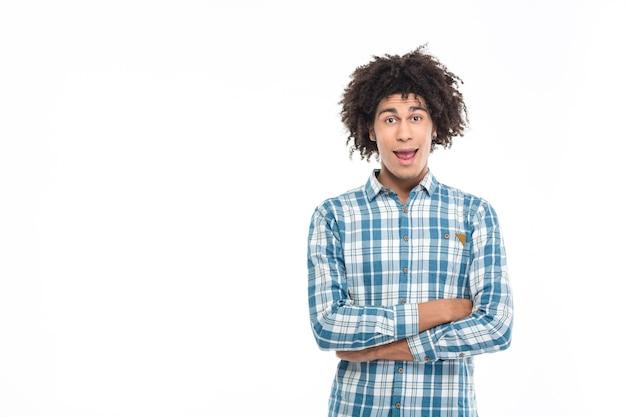 Portret wesołego afroamerykańskiego mężczyzny stojącego z założonymi rękoma na białym tle na białej ścianie