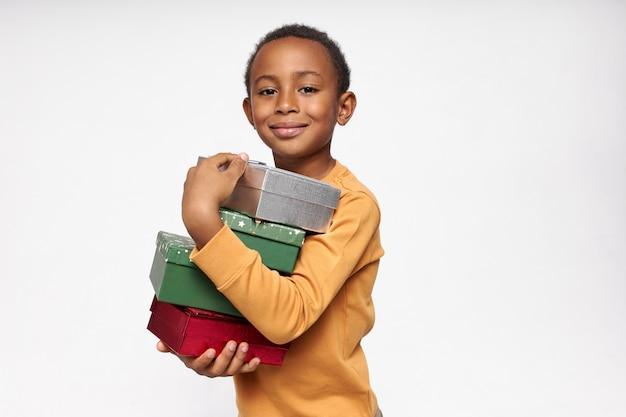 Portret wesołego afrykańskiego chłopca niosącego pudełka, odbierającego prezenty, patrząc na przód z radosnym, szczęśliwym uśmiechem