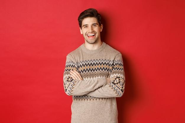 Portret wesołego, atrakcyjnego mężczyzny w świątecznym swetrze, śmiejącego się i uśmiechającego, świętującego nowy rok i ferie zimowe, stojącego na czerwonym tle
