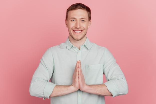 Portret wesołego, atrakcyjnego, pełnego nadziei faceta, który ręce razem, promienny uśmiech, proszę na różowym tle