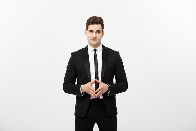 Portret wesołego, atrakcyjnego, przystojnego biznesmena trzymającego się za ręce z pewną siebie twarzą, patrzącego na kamerę stojącą na szarym tle