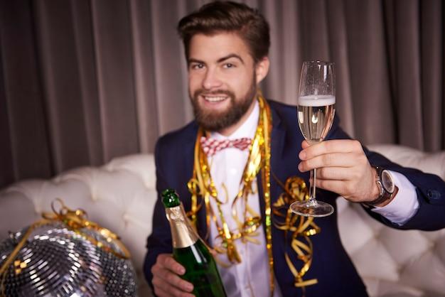 Portret wesołego biznesmena z opiekaniem szampana
