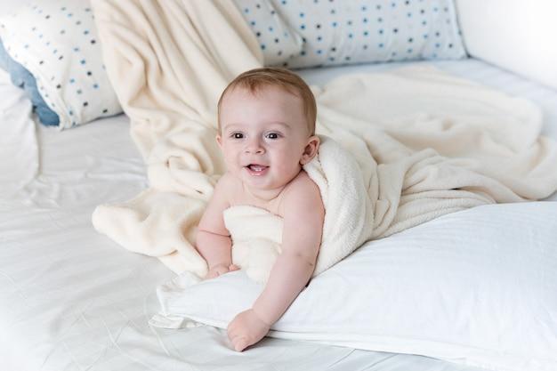 Portret wesołego chłopca leżącego na dużej poduszce pod białym kocem