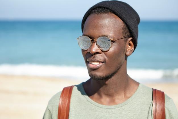 Portret wesołego czarnoskórego podróżnika korzystającego z letnich wakacji nad morzem, wyglądającego na beztroskiego i zrelaksowanego, w modnym kapeluszu i okularach przeciwsłonecznych z lustrzanymi soczewkami. turystyka, podróże, ludzie i styl życia