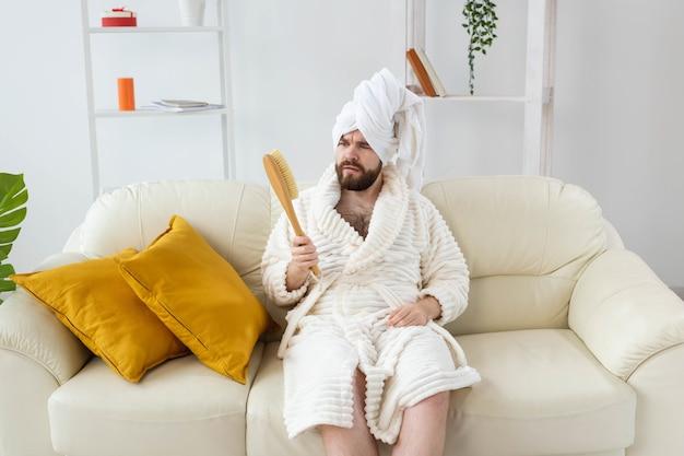 Portret wesołego faceta nosić turban ręcznik trzymający w dłoniach pędzel do masażu, gdy siedzi na kanapie male