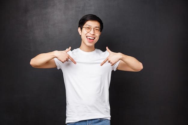 Portret wesołego fajnego przyjaznego azjatyckiego faceta wskazującego na link, wskazującego reklamę u dołu, zapraszającego sprawdź coś niesamowitego, zorganizuj imprezę i spytaj, uśmiechnij się