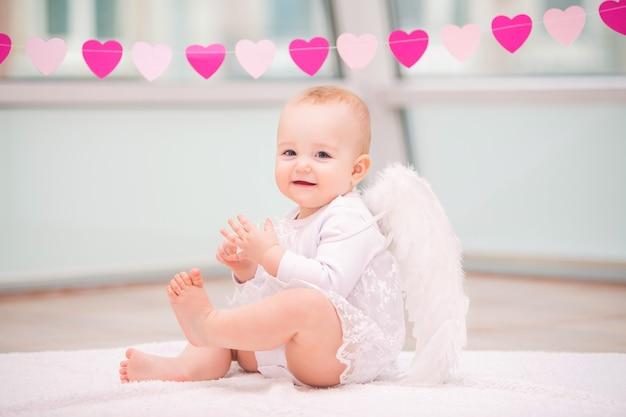 Portret wesołego figlarnego dziecka z białymi anielskimi skrzydłami