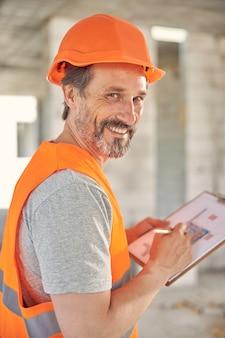 Portret wesołego inżyniera z ołówkiem i schowkiem pozującym do kamery