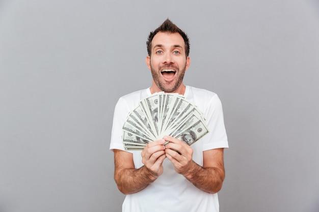 Portret wesołego mężczyzny trzymającego banknoty dolarowe na szarym tle